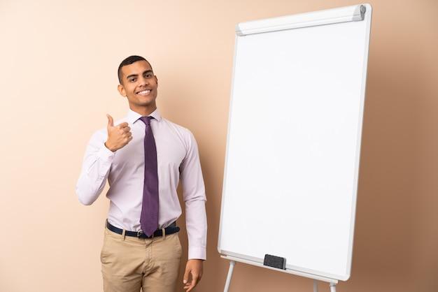 Hombre de negocios joven sobre la pared aislada que da una presentación en el tablero blanco y con los pulgares para arriba