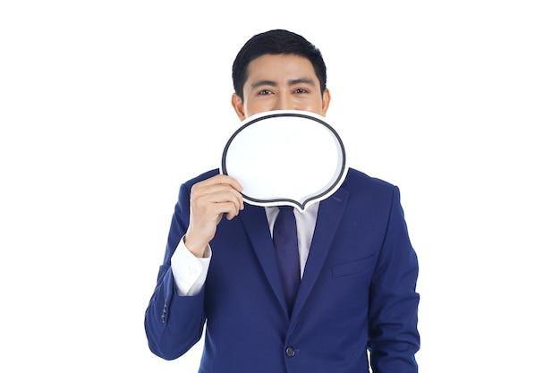 Hombre de negocios joven sonriente asiático feliz que sostiene el discurso de la burbuja, aislado en el fondo blanco