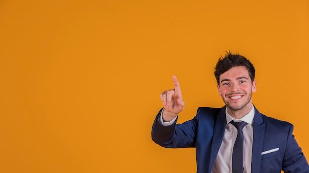 Hombre de negocios joven sonriente contra señalar su dedo hacia arriba contra fondo anaranjado