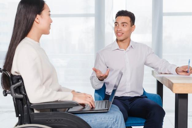 Hombre de negocios joven sonriente y mujer discapacitada que tiene discusión en la oficina