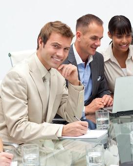 Hombre de negocios joven sonriente que hace notas