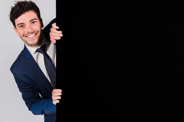 Hombre de negocios joven sonriente que mira a escondidas del cartel negro