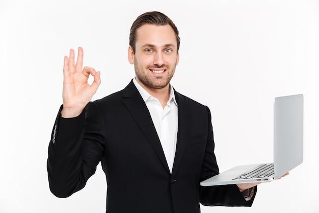 Hombre de negocios joven sonriente que muestra gesto aceptable usando la computadora portátil.