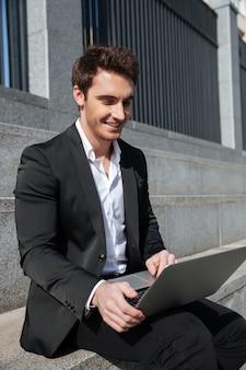 Hombre de negocios joven sonriente que se sienta al aire libre usando la computadora portátil