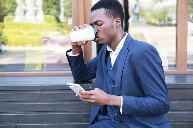 Hombre de negocios joven sonriente que se sienta en el banco que bebe el café