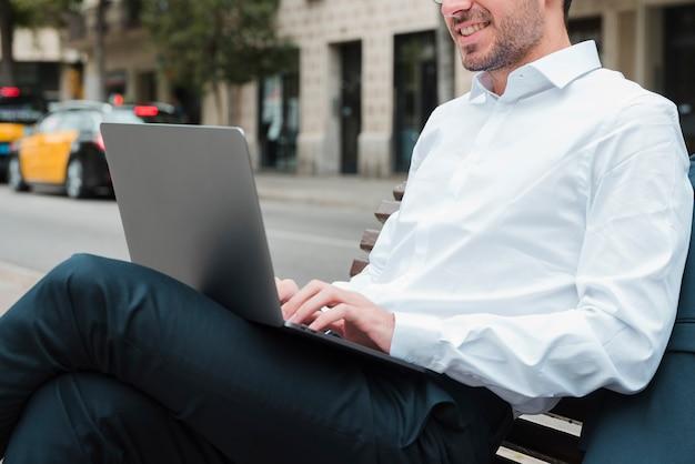 Hombre de negocios joven sonriente que se sienta en banco usando el ordenador portátil
