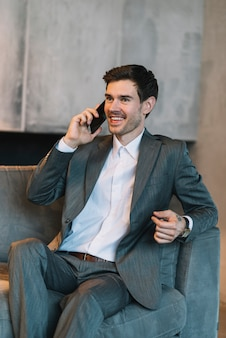 Hombre de negocios joven sonriente que se sienta en el sofá que habla a través del teléfono móvil