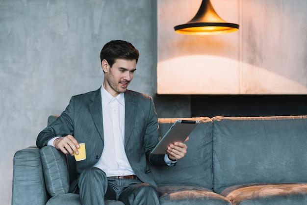 Hombre de negocios joven sonriente que se sienta en el sofá que sostiene la taza de café y la tableta digital