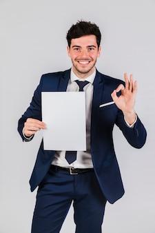 Hombre de negocios joven sonriente que sostiene el libro blanco en la mano que muestra la muestra aceptable