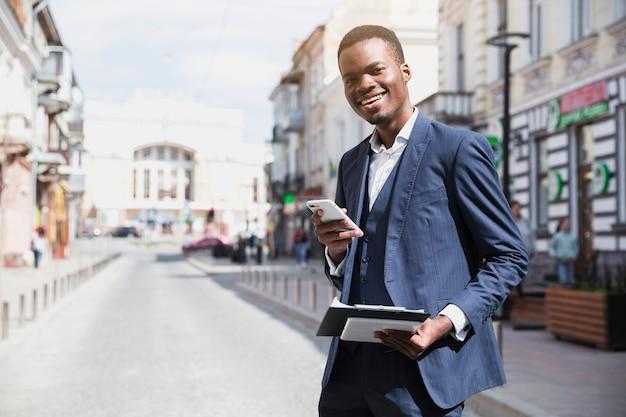 Hombre de negocios joven sonriente que sostiene el tablero y el teléfono móvil en la mano que se coloca en el camino en ciudad