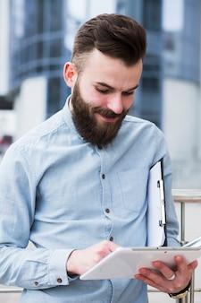 Hombre de negocios joven sonriente que sostiene el tablero usando la tableta digital