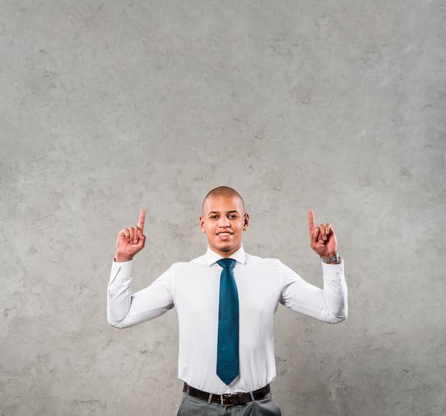 Hombre de negocios joven sonriente con sus brazos levantados apuntando su dedo hacia arriba contra la pared gris