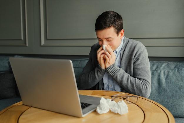El hombre de negocios joven sopla su nariz mientras que trabaja en su computadora portátil en el lugar de trabajo.