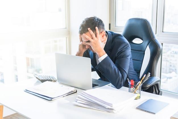 Hombre de negocios joven subrayado que se sienta en el lugar de trabajo en la oficina