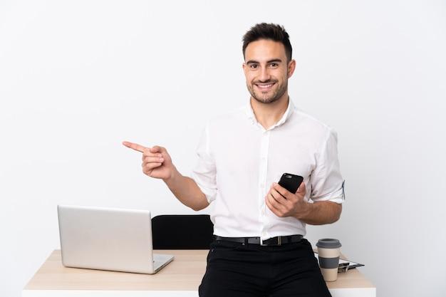 Hombre de negocios joven con un teléfono móvil en un lugar de trabajo que señala el dedo al lado
