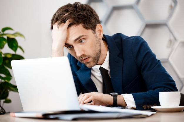 Hombre de negocios joven trastornado que se sienta en la computadora portátil, fondo de la oficina.