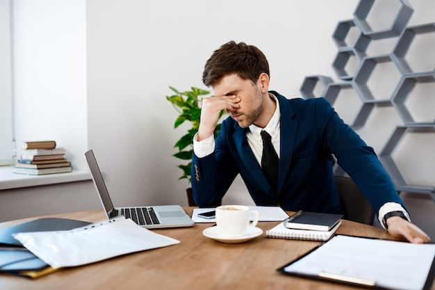 Hombre de negocios joven trastornado que se sienta en el lugar de trabajo, fondo de la oficina.