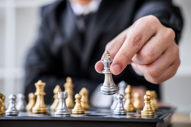 Hombre de negocios jugando ajedrez a análisis de desarrollo nuevo plan de estrategia.
