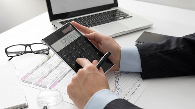 Hombre de negocios de lado calculando números de finanzas