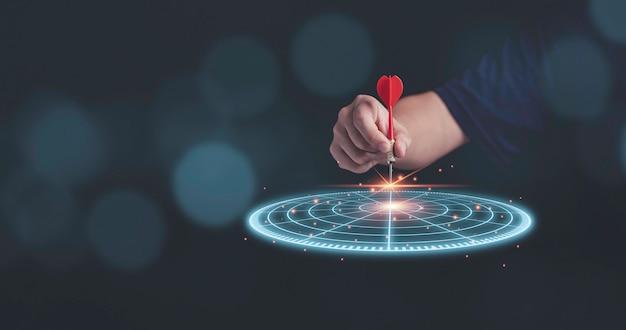 Hombre de negocios lanzando dardos de flecha roja al tablero de dardos de destino virtual. configurar objetivos y destino para el concepto de inversión empresarial.