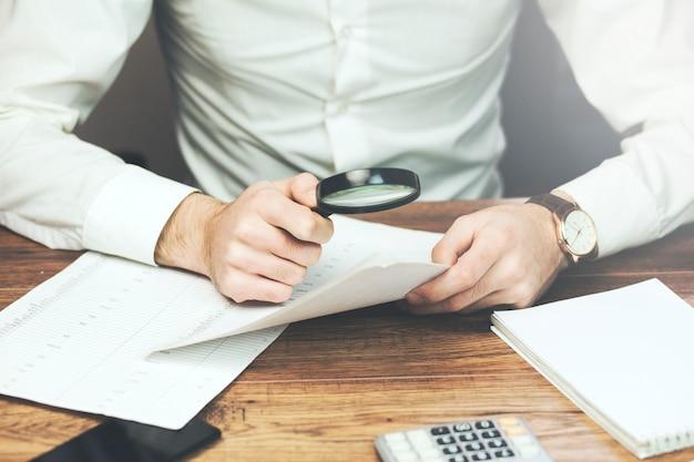 Hombre de negocios leyendo documentos con lupa