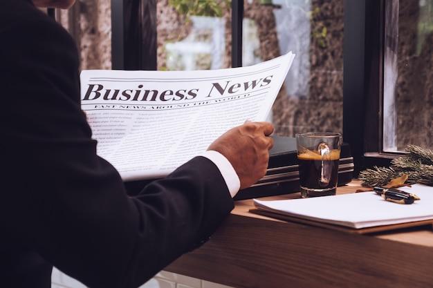 El hombre de negocios está leyendo el periódico en el café
