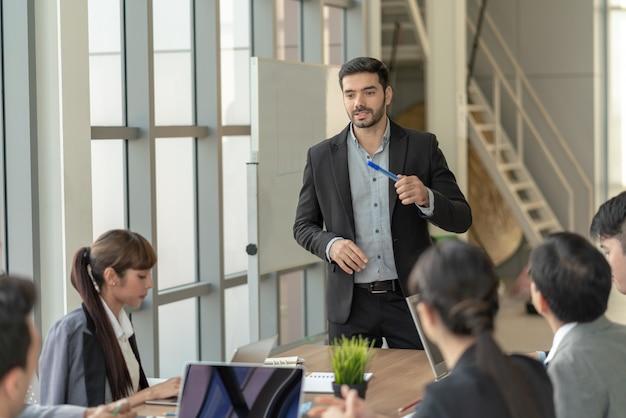 Hombre de negocios líder que se presenta al trabajo mientras se reúne con colegas en la oficina. presentación de la reunión del equipo de negocios, concepto de planificación de la conferencia