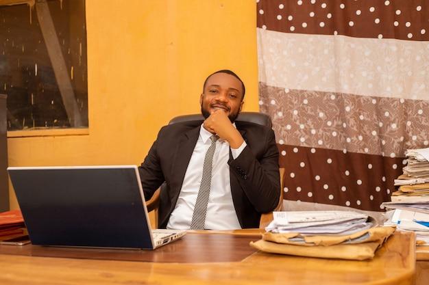 Hombre de negocios lindo que se siente emocionado en la oficina