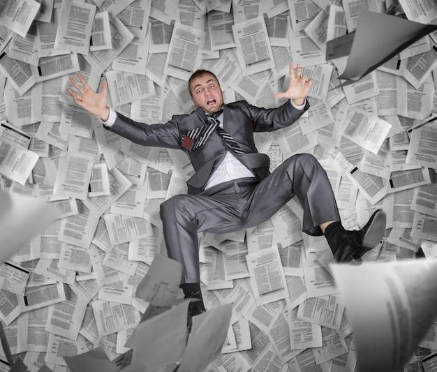 Hombre de negocios loco entre la pila de papeles e informes, burocracia y papeleo en los negocios