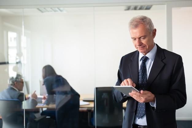 Hombre de negocios maduro centrado que usa la tableta mientras sus colegas discuten el proyecto en el lugar de trabajo detrás de la pared de cristal. copie el espacio. concepto de comunicación