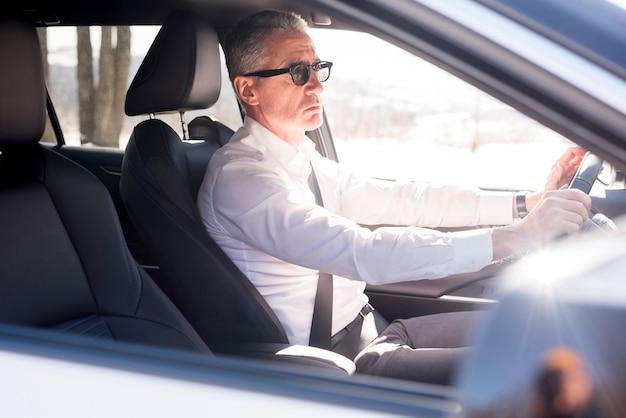 Hombre de negocios maduro conduciendo