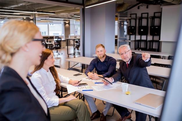 Hombre de negocios maduro curioso que señala el dedo en el rotafolio en la presentación