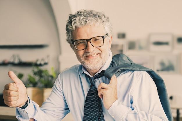 Hombre de negocios maduro feliz de pie en la cafetería de la oficina, apoyado en el mostrador, sosteniendo la chaqueta sobre el hombro, mostrando el pulgar hacia arriba