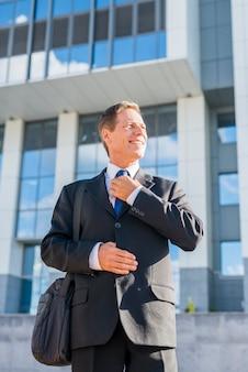 Hombre de negocios maduro feliz en traje negro con el edificio de oficinas en fondo