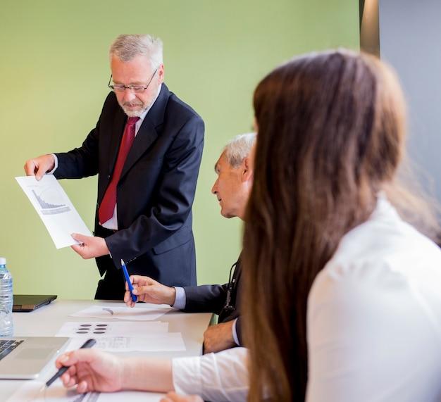 Hombre de negocios maduro que muestra el gráfico a su socio comercial en la oficina