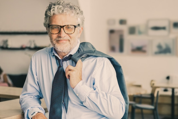 Hombre de negocios maduro relajado positivo de pie en la cafetería de la oficina, apoyado en el mostrador, sosteniendo la chaqueta sobre el hombro