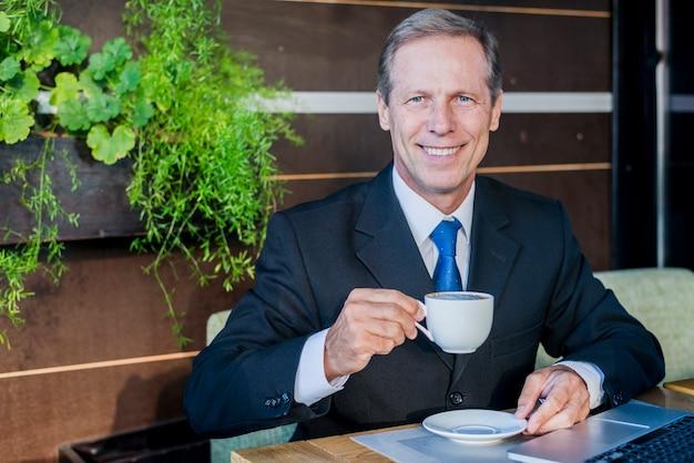Hombre de negocios maduro sonriente que bebe el café en caf�