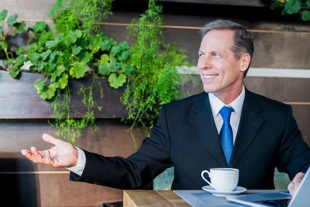 Hombre de negocios maduro sonriente que hace gesto de mano con la taza de café y de ordenador portátil en el escritorio