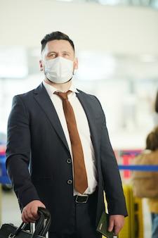 Hombre de negocios maduro en traje elegante y máscara protectora de pie en el salón del aeropuerto contemporáneo mientras espera el vuelo
