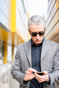 Hombre de negocios maduro usando móvil