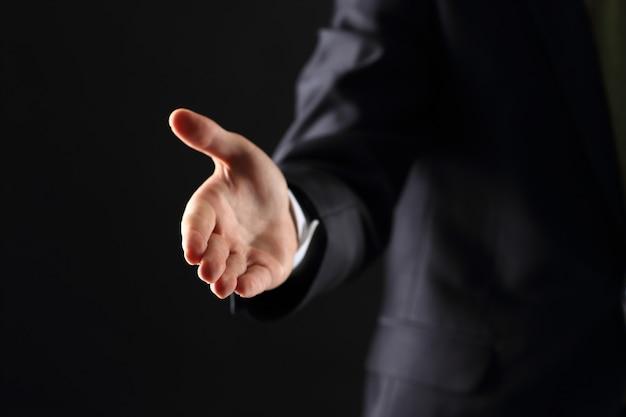 Un hombre de negocios con la mano abierta listo para sellar un trato.