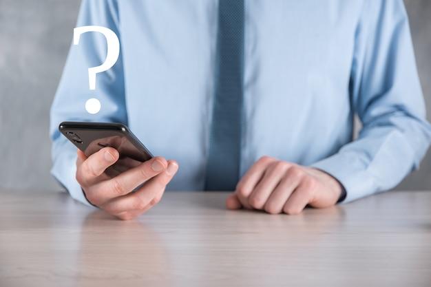 Hombre de negocios, mano, asimiento, interfaz, interrogación, signo, web pregunte en línea, concepto de preguntas frecuentes, qué, dónde, cuándo, cómo y por qué, busque información en internet.
