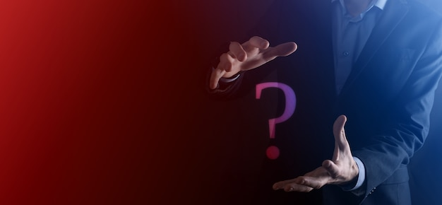 Hombre de negocios, mano, asimiento, interfaz, signos de interrogación, señal, web. pregunte preguntas en línea, concepto de preguntas frecuentes, qué, dónde, cuándo, cómo y por qué, busque información en internet