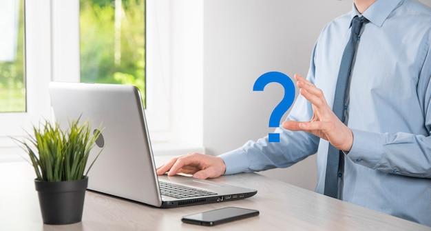 Hombre de negocios, mano, asimiento, interfaz, signos de interrogación, señal, web. pregunte quiestion en línea, concepto de preguntas frecuentes, qué