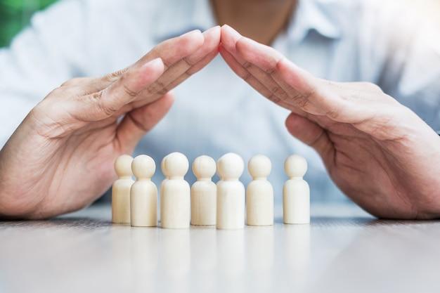 Hombre de negocios mano cubierta hombre madera de multitud de empleados. conceptos de personas, negocios, gestión de recursos humanos, seguros de vida, trabajo en equipo y liderazgo