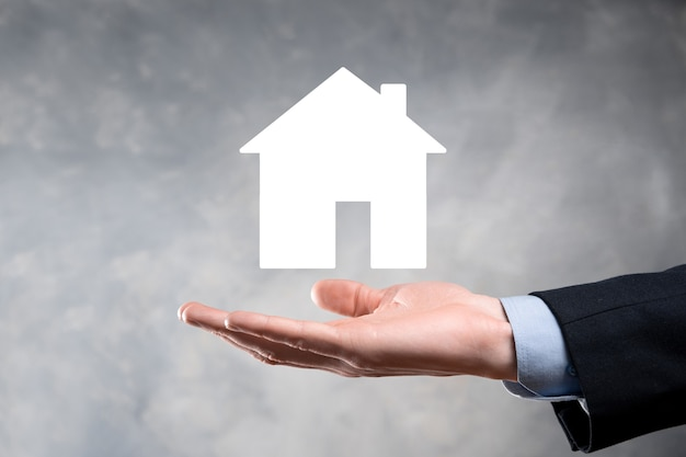 Hombre de negocios mano sosteniendo el icono de la casa sobre fondo azul. seguro de propiedad y concepto de seguridad concepto de bienes raíces bandera con espacio de copia.
