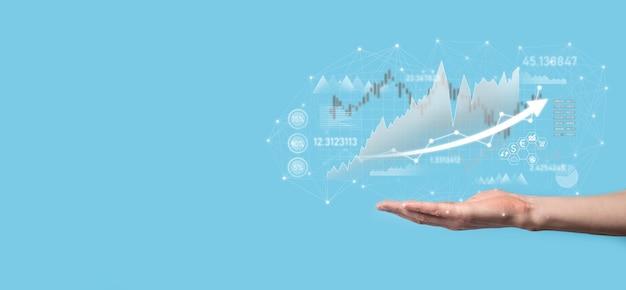 El hombre de negocios en la mano sostiene el gráfico de las finanzas del negocio bancario e invierte en el punto de inversión del mercado de valores, el crecimiento económico y el concepto del inversor.
