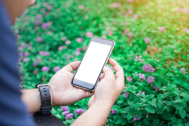 Hombre de negocios manos sosteniendo teléfono móvil de pantalla en blanco