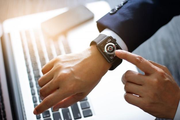 Hombre de negocios manos tocando reloj inteligente. usando una aplicación de bolsa y un gráfico en la pantalla virtual moderna para negocios.