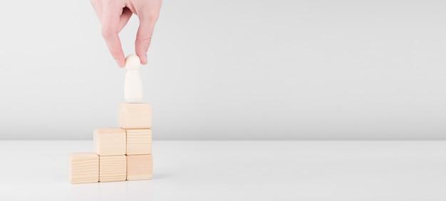 El hombre de negocios mantenga al hombre de madera que representa al líder pasos hacia el éxito de pie